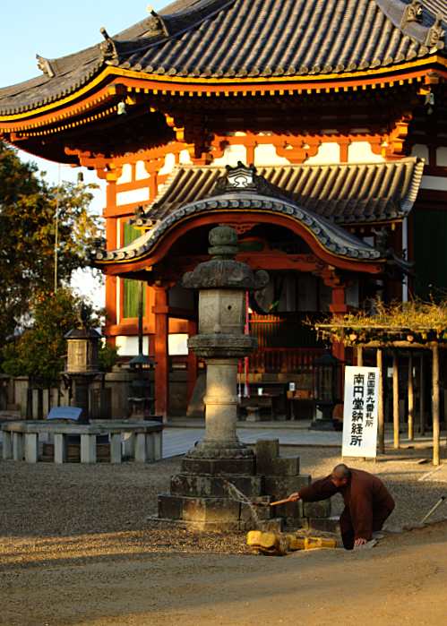 Sunrise at a temple in Nara, where a monk is throwing water around.